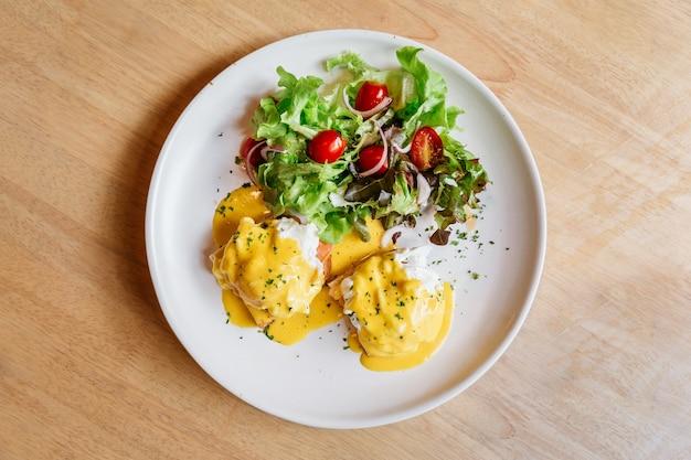 Vue de dessus de l'oeuf benedict servi avec une salade. Photo Premium