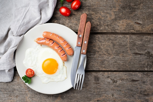 Vue De Dessus De L'oeuf Du Petit Déjeuner Et Des Saucisses Sur Une Plaque Avec Des Tomates Et Des Couverts Photo gratuit