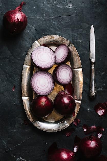 Vue de dessus des oignons rouges sur une assiette et un couteau Photo gratuit