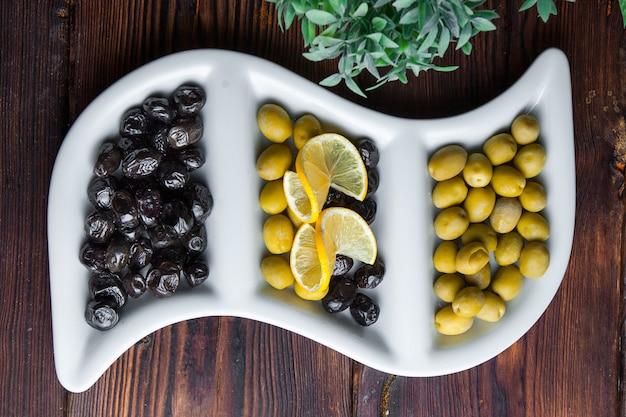 Vue De Dessus Olives Olives Au Citron Sur Une Plaque Frisée Blanche Photo gratuit