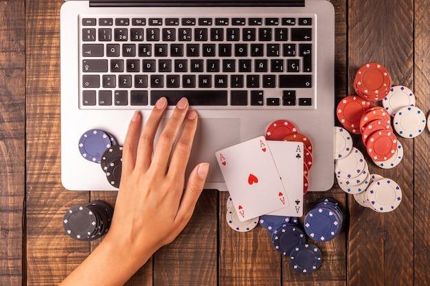 Vue de dessus d'un ordinateur avec des jetons de poker et des cartes pour parier ou jouer. Photo Premium