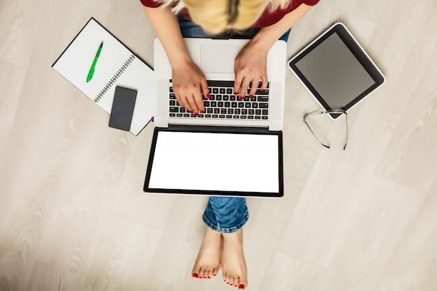 Vue de dessus d'un ordinateur portable dans les mains de la fille assise sur un plancher en bois avec café Photo Premium