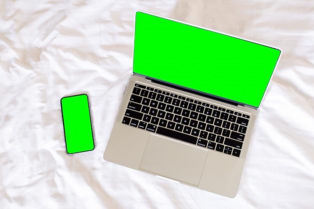 Vue de dessus ordinateur portable à écran vert vide et téléphone intelligent, Photo Premium