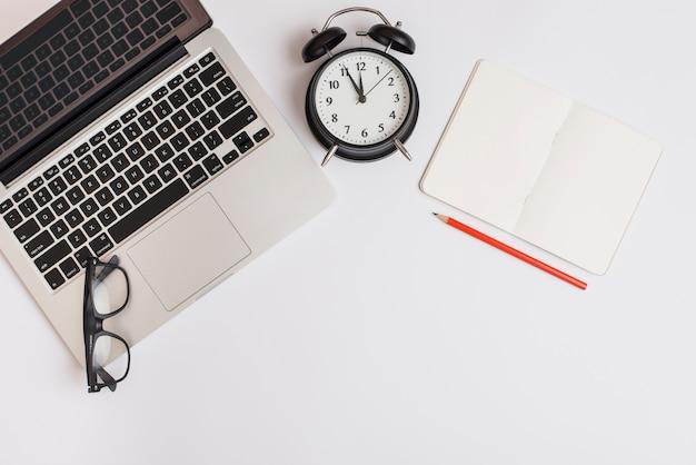 Une vue de dessus d'un ordinateur portable; réveil; crayon; cahier et lunettes sur fond blanc Photo gratuit