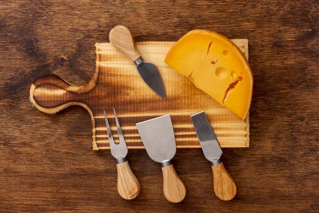 Vue de dessus des outils avec une tranche de fromage sur une table Photo gratuit