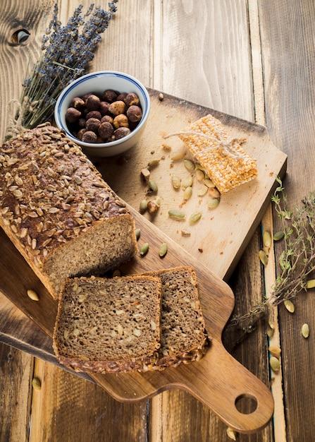 Une vue de dessus de pain bio et barre énergétique sur planche à découper Photo gratuit