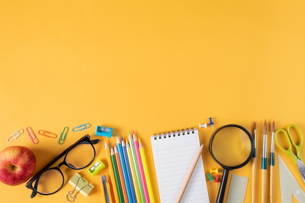 Vue de dessus de papeterie ou de fournitures scolaires sur fond jaune Photo Premium