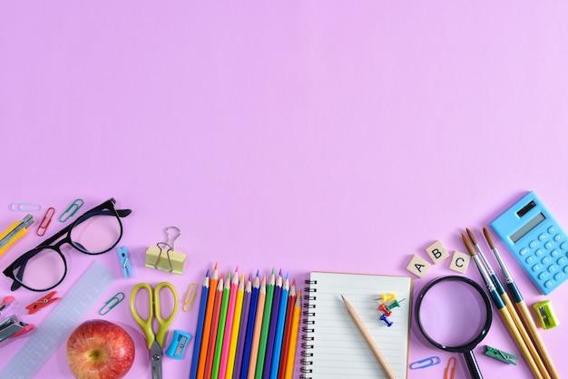 Vue de dessus de papeterie ou de fournitures scolaires avec des livres, des crayons de couleur, une calculatrice, un ordinateur portable, des clips et une pomme rouge sur fond rose. Photo Premium