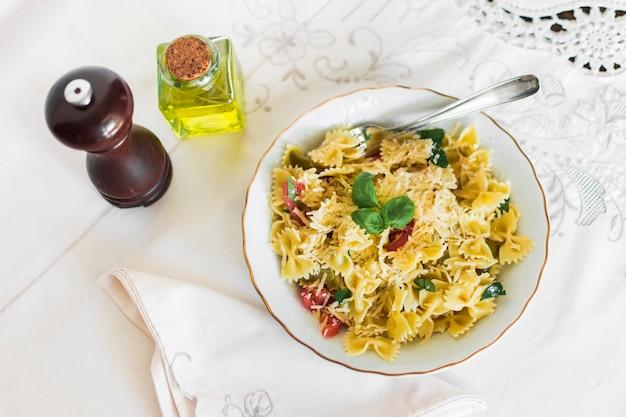 Une vue de dessus de pâtes farfalle avec du fromage; tomates et feuille de basilic dans l'assiette Photo gratuit