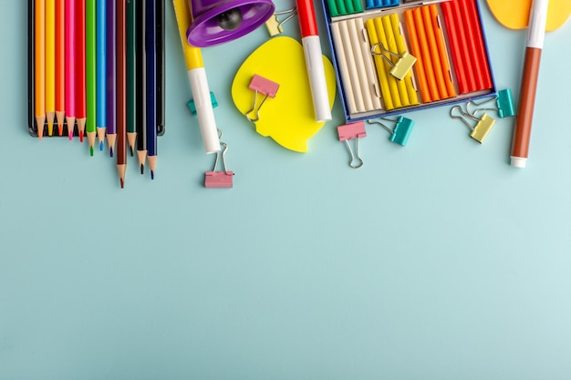 Vue De Dessus Des Pâtes à Modeler Colorées Avec Des Crayons De Couleur Sur Le Livre Bleu Des Enfants De L'école De Couleur Bureau Enfants Photo gratuit
