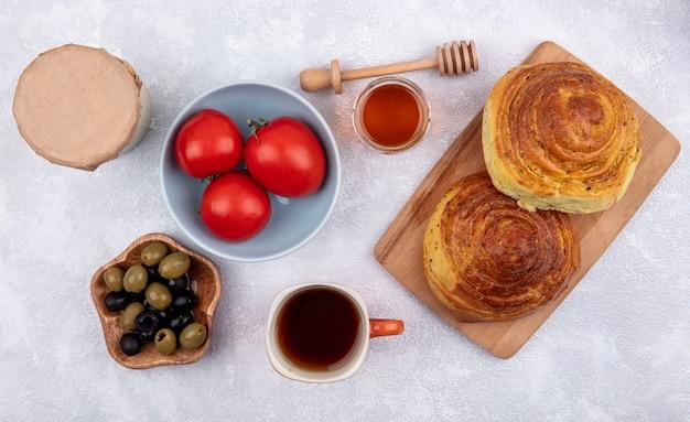Vue De Dessus De La Pâtisserie Traditionnelle Azerbaïdjanaise Gogal Sur Une Planche De Cuisine En Bois Avec Des Olives Sur Un Bol En Bois Avec Des Tomates Fraîches Sur Un Bol Sur Un Fond Blanc Photo gratuit