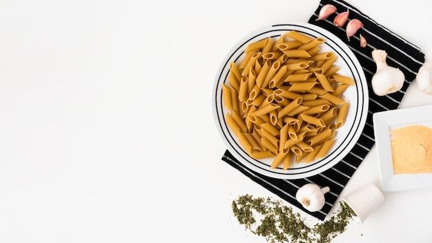 Vue de dessus des penne crues et de ses ingrédients sur fond blanc Photo gratuit