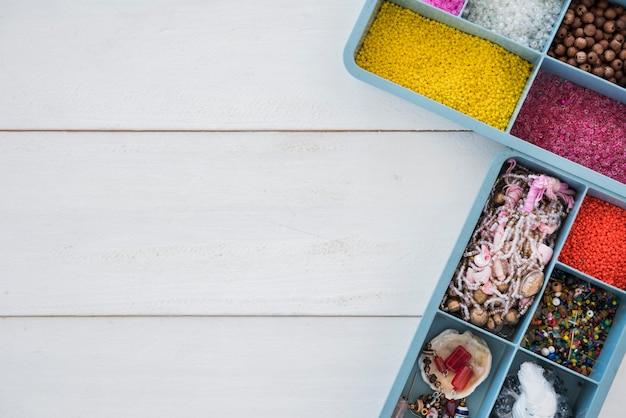 Une vue de dessus de perles colorées dans un étui bleu sur un bureau en bois blanc Photo gratuit
