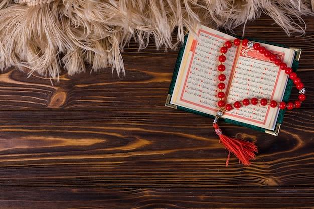 Une vue de dessus de perles de prière avec un livre sacré islamique sur un bureau en bois Photo gratuit