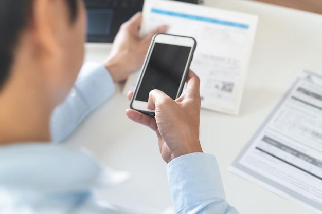 Vue de dessus de la personne payant des factures via une application bancaire par téléphone mobile. Photo Premium