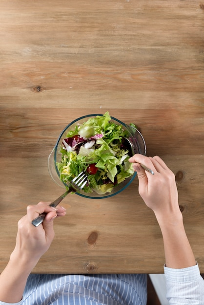 Vue de dessus d'une personne préparant une salade saine dans un bol Photo gratuit