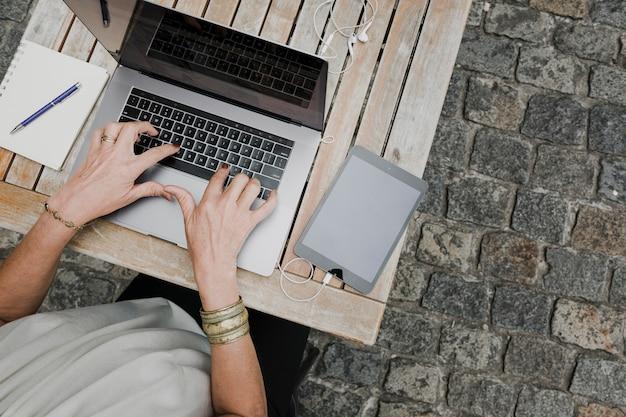Vue De Dessus De La Personne Qui Tape Sur Un Ordinateur Portable à L'extérieur Photo gratuit