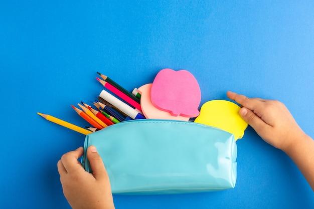 Vue De Dessus Petit Enfant Tenant Une Boîte De Stylo Bleu Pleine De Crayons Colorés Sur Une Surface Bleue Photo gratuit