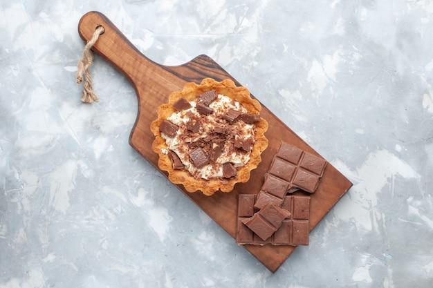 Vue De Dessus Petit Gâteau Crème Avec Des Barres De Chocolat Sur Le Fond Blanc Gâteau Sucré Sucre Crème Chocolat Photo gratuit