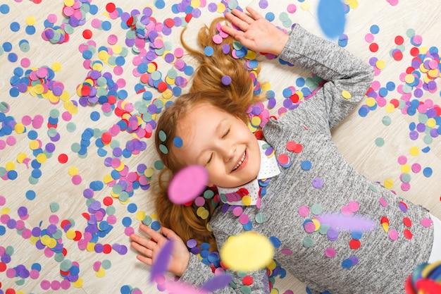Vue de dessus d'une petite fille gisant sur le sol sous la chute de confettis. Photo Premium