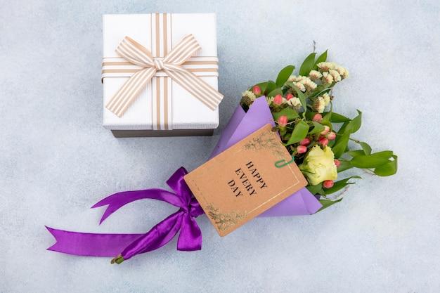 Vue De Dessus De Petites Et Merveilleuses Fleurs Et Boîte-cadeau Sur Une Surface Blanche Photo gratuit