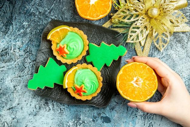 Vue De Dessus Petites Tartes Biscuits Arbre De Noël Sur Plaque Noire Ornement De Noël Coupé Orange En Main Féminine Sur Table Grise Photo gratuit