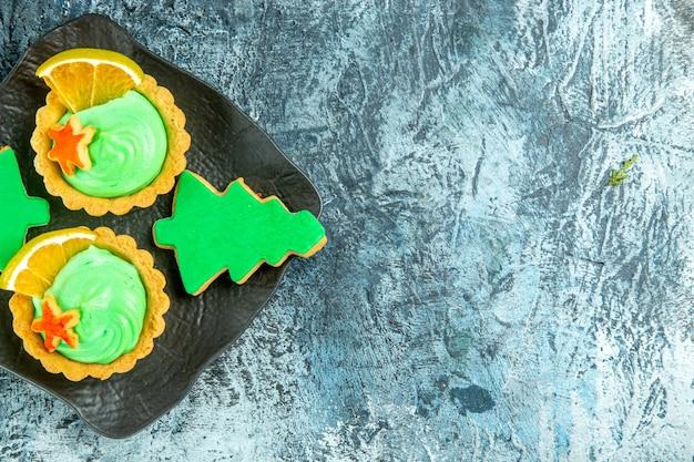 Vue De Dessus Petites Tartes Avec Des Biscuits De Noël Crème Pâtissière Verte Sur Plaque Noire Sur Table Grise Avec Espace Copie Photo gratuit