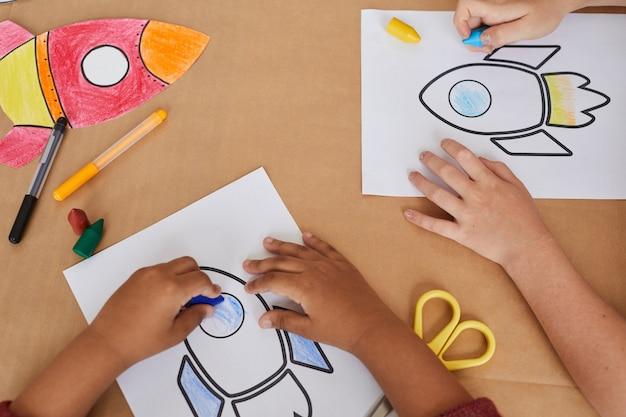 Vue De Dessus Petits Enfants Méconnaissables Dessinant Des Images De Fusées Spatiales Tout En Profitant D'un Cours D'art à L'école Maternelle Ou Dans Un Centre De Développement Photo Premium