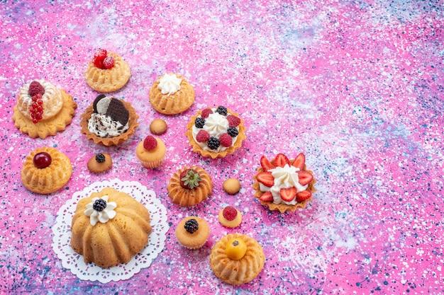 Vue De Dessus Petits Gâteaux Délicieux Avec De La Crème Avec Différentes Baies Sur Le Fond Clair-lumineux Gâteau Biscuit Berry Sweet Bake Photo gratuit