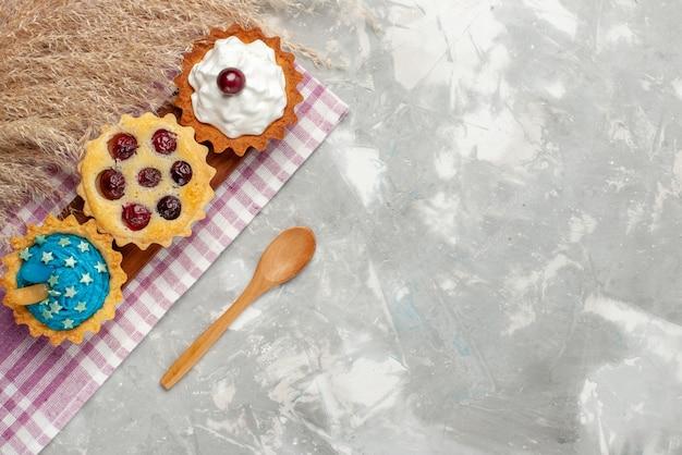Vue De Dessus Petits Gâteaux Délicieux Avec De La Crème Et Des Fruits Sur Le Fond Clair Gâteau Crème Douce Cuire Les Fruits Photo gratuit