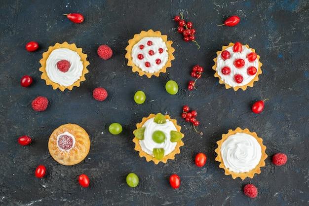 Vue De Dessus Petits Gâteaux Délicieux Avec De La Crème Et Des Fruits Frais Sur Le Fruit Du Bureau Noir Photo gratuit