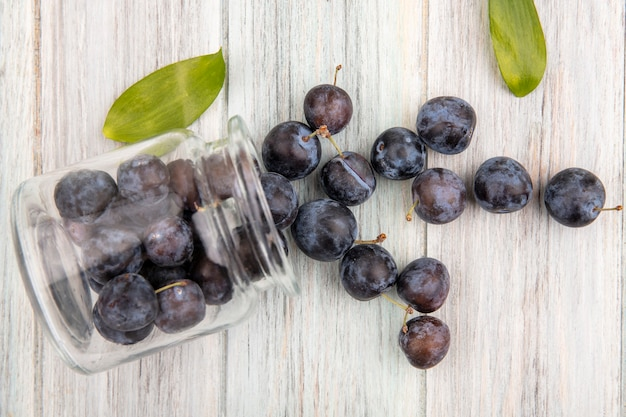 Vue De Dessus Des Petits Prunelles Bleu-noir Aigre Tombant D'un Bocal En Verre Avec Des Feuilles Sur Un Fond En Bois Gris Photo gratuit