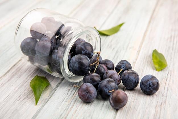 Vue De Dessus Des Petits Prunelles Bleu-noir Aigre Tombant D'un Bocal En Verre Sur Un Fond En Bois Gris Photo gratuit