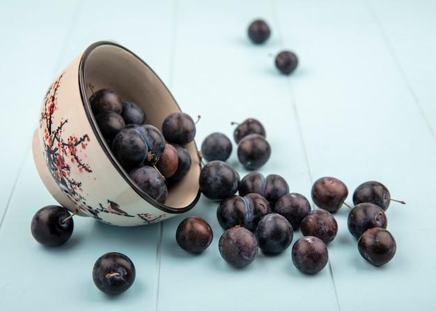 Vue De Dessus Des Petits Prunelles Bleu-noir Aigre Tombant D'un Bol Sur Un Fond Bleu Photo gratuit