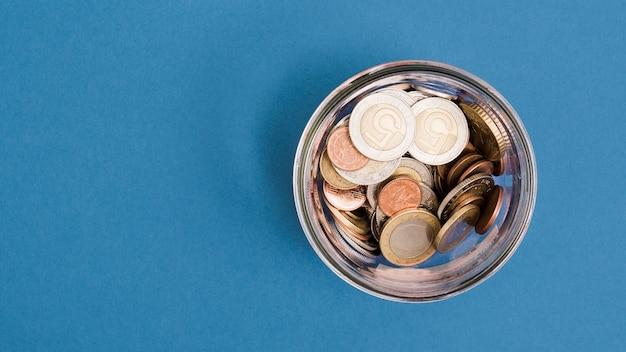 Une vue de dessus des pièces de monnaie dans le bocal en verre sur fond bleu Photo gratuit