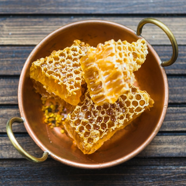 Une vue de dessus de pièces en nid d'abeilles dans l'ustensile en cuivre avec poignées Photo gratuit