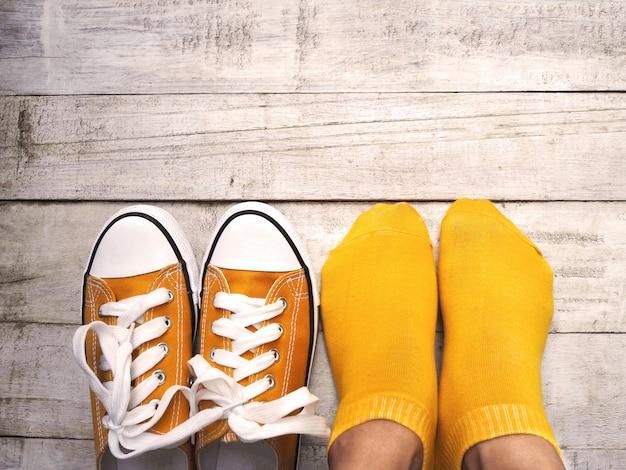 Vue dessus, de, pieds femme, porter, chaussettes jaunes, et, sneaker, sur, bois Photo Premium