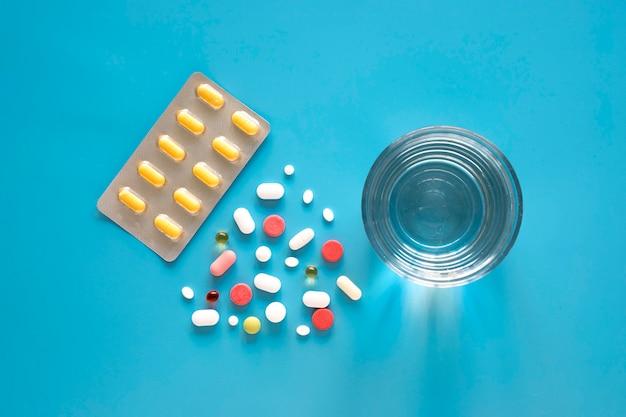 Vue De Dessus Des Pilules En Forme De Triangle Et De Papier D'aluminium Avec Un Verre D'eau Photo gratuit