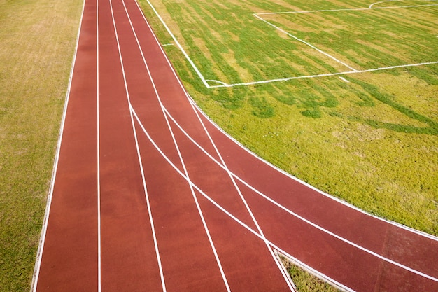 Vue de dessus des pistes de course rouges et de la pelouse d'herbe verte. infrastructure pour les activités sportives. Photo Premium
