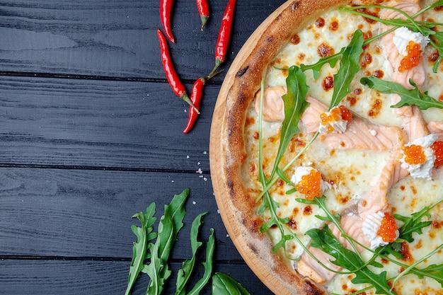Vue De Dessus Pizza Au Saumon, Roquette, Caviar Rouge, Fromage Sur Fond De Bois Foncé Avec Copie Sapce. Pizza Italienne Aux Fruits De Mer. Contexte Alimentaire. Délicieuse Pizza De Cuisine Italienne Faite Maison Photo Premium