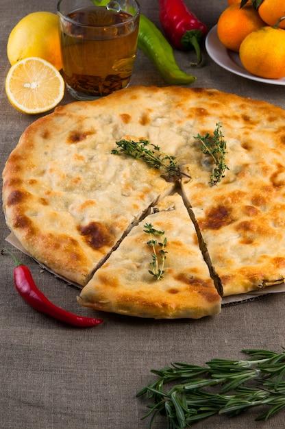 Vue de dessus de la pizza calzone ou de la tourte aux champignons au poulet avec poivre, citron, romarin et thé sur fond de toile de lin Photo Premium