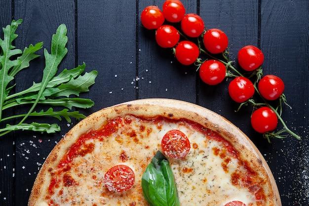 Vue De Dessus De Pizza Margarita. Mise à Plat De Nourriture Avec Pizza, Tomate Et Roquette Sur Fond En Bois Noir. Pizza Italienne Maison. Cuisine Italienne. Copiez L'espace. Vue D'en-haut. Nourriture Végétalienne Photo Premium