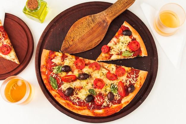 Une vue de dessus de la pizza sur une planche en bois avec une spatule Photo gratuit