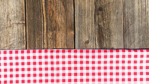 Vue de dessus d'une planche de bois et d'une nappe à carreaux Photo gratuit