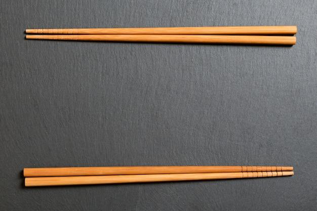 Vue de dessus sur une plaque d'ardoise noire avec des baguettes en bois sur dark Photo Premium