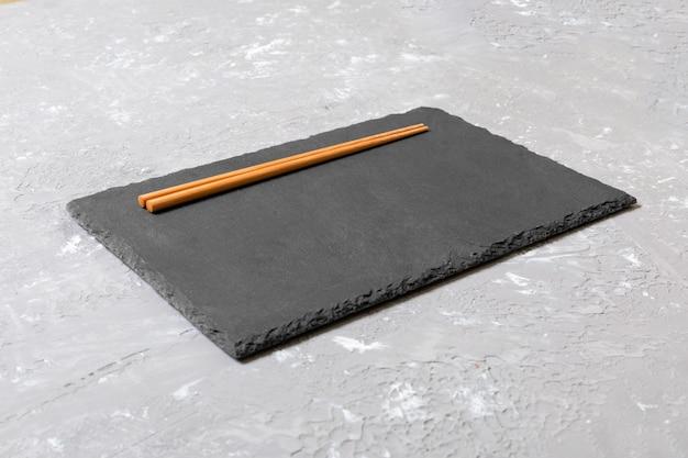 Vue de dessus sur une plaque d'ardoise noire avec des baguettes en bois sur fond sombre, espace copie Photo Premium