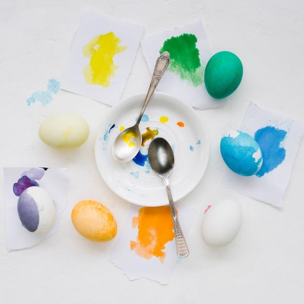 Vue De Dessus De La Plaque Avec Des Cuillères Et Des œufs Colorés Pour Pâques Photo gratuit