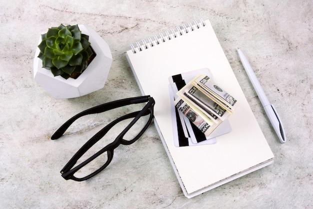 Vue de dessus plat cahier poser, stylo, argent, cartes de crédit, lunettes et succulent sur une table de marbre Photo Premium