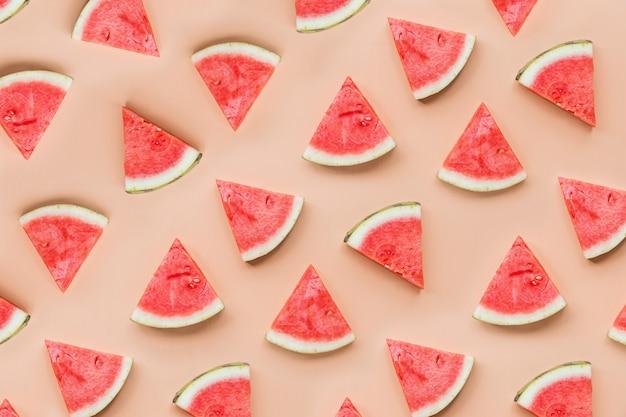 Vue de dessus plat créatif poser des tranches de melon d'eau fraîche sur fond de table orange Photo Premium