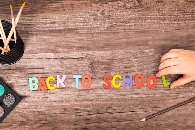 Vue de dessus plat laïc mains de garçon jouent l'alphabet à l'école sur fond en bois avec espace de copie Photo Premium